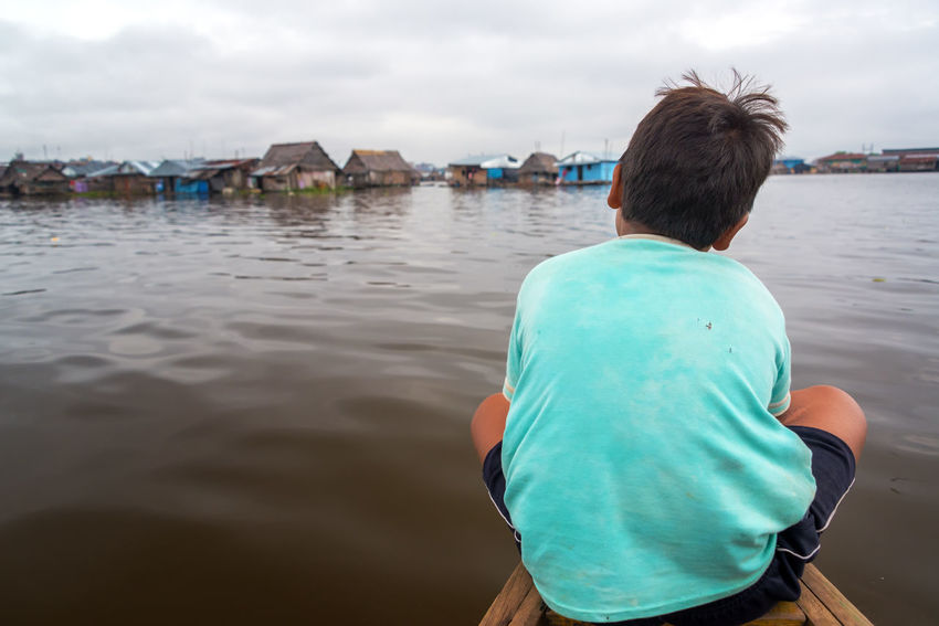 IQUITOS, PERU - MARCH 17: Young boy on the front of a wooden in Belen neighborhood of Iquitos, Peru on March 17, 2015 Amazon Amazon River Amazonas Amazonia Architecture Belén Boat Boy Building Exterior Canoe Day Iquitos  Latin America One Person Outdoors Peru Peruvian Real People River Shacks Sky Slum South America Water