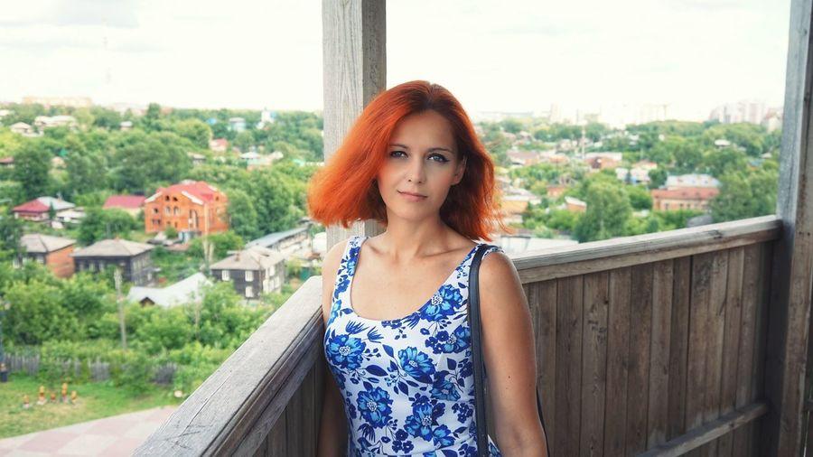 Portrait of redhead woman standing in gazebo