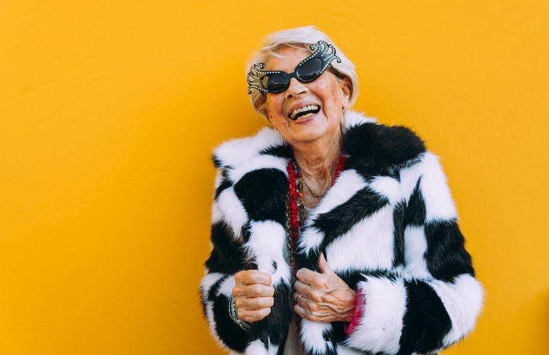 Portrait of senior woman laughing while standing against yellow background