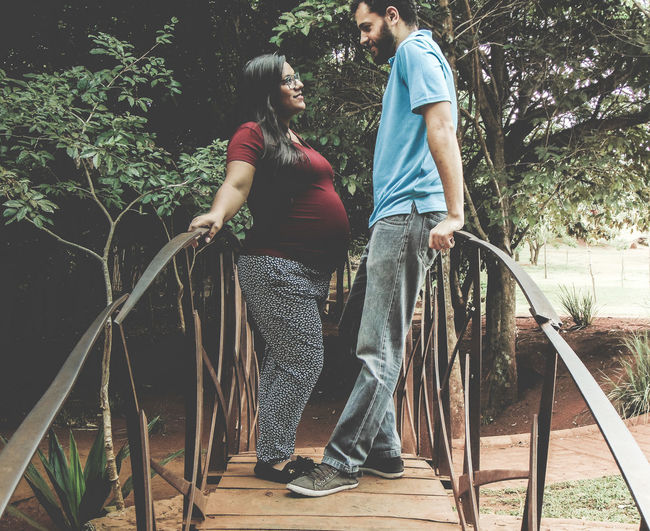 Side view of couple standing on footbridge