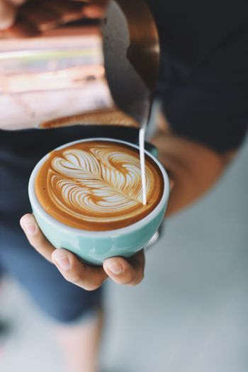 Midsection Of Person Pouring Milk In Coffee