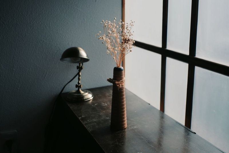 Close-up of vase on table by window at home