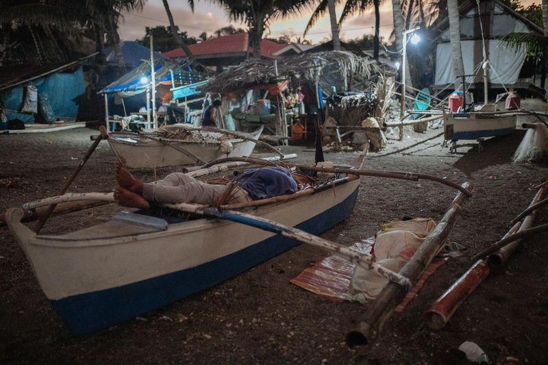 People sleeping on boat at beach