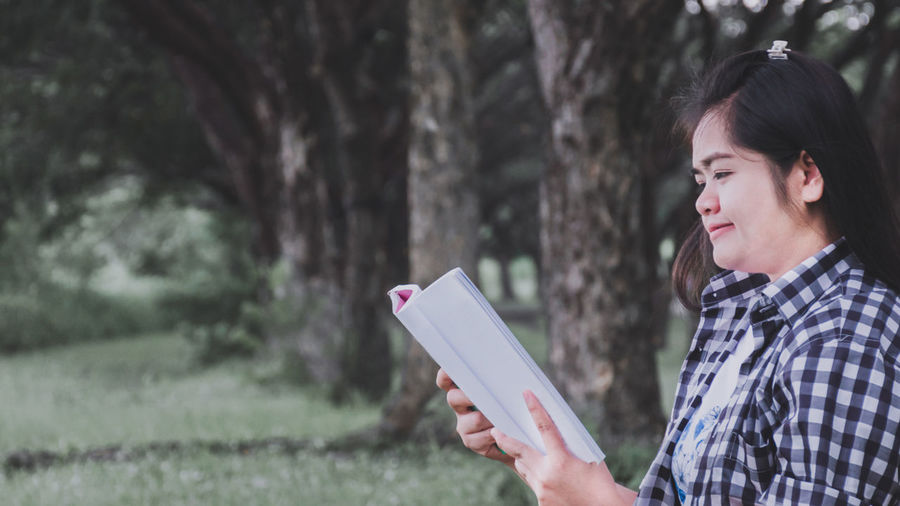 Side view of woman reading book in park