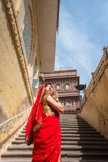 Woman in red sari standing against temple