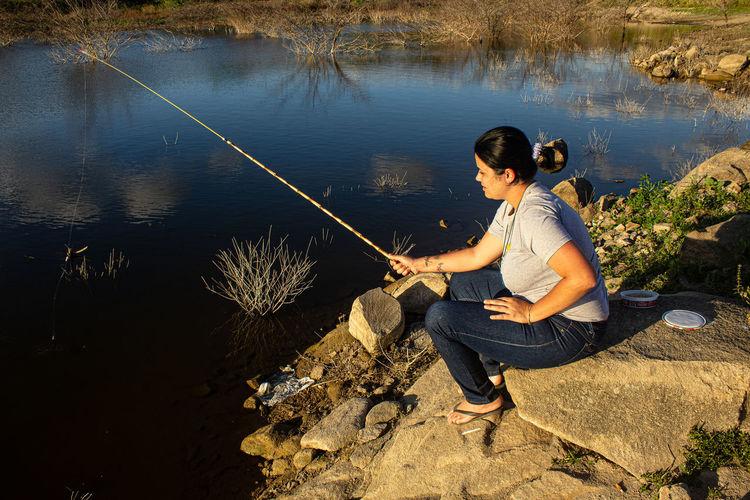 Full length of woman fishing at lake