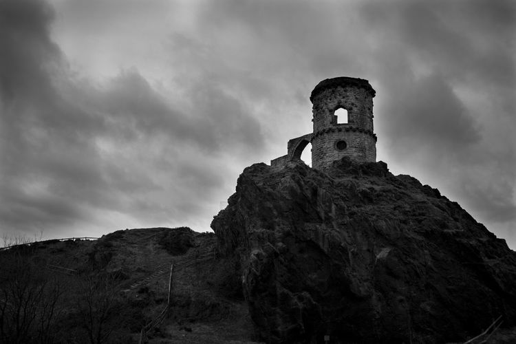Low angle view of old castle ruin on rock formation against sky