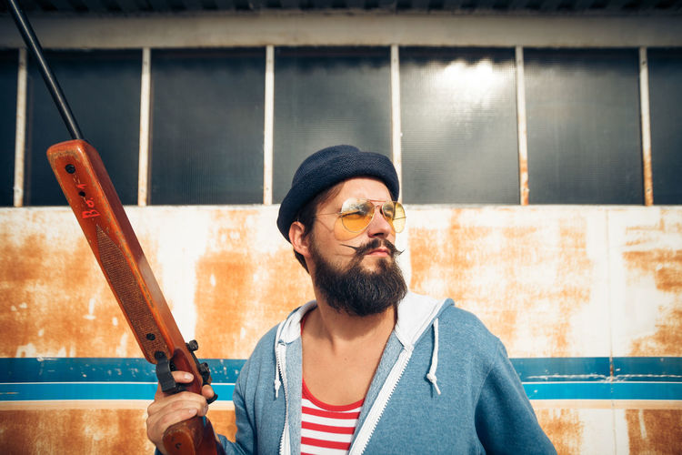 Gun Heroic Hunter Man Shoot Stripes Target Adult Airgun Beard Casual Clothing Facial Hair Front View Hipster Holding Jumpsuit Looking Males  One Person Onsie Portrait Pose Pyjama Riffle Weapon The Portraitist - 2018 EyeEm Awards