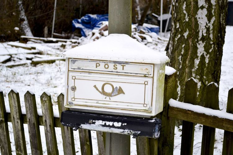 Snow on old post box with text on fence during winter