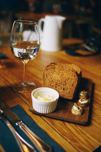 Bread and Butter Food And Drink Refreshment Table Drink Glass Freshness Food Alcohol Wine Wineglass Focus On Foreground Indoors  Wood - Material No People Still Life Close-up Drinking Glass Ready-to-eat Household Equipment Transparent Temptation Bread