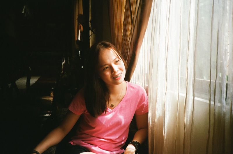 Portrait of a smiling young woman sitting by window