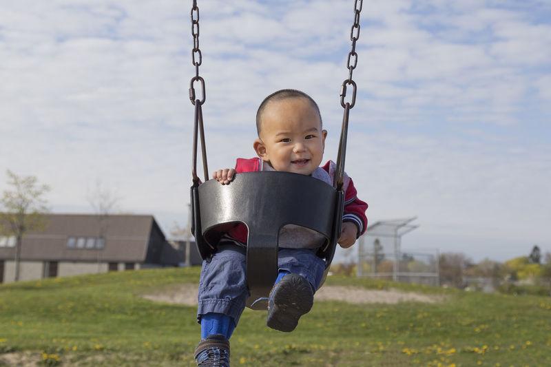 Portrait of cute baby boy sitting on swing against cloudy sky