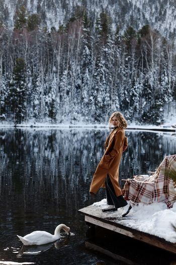 Woman by lake against trees during winter