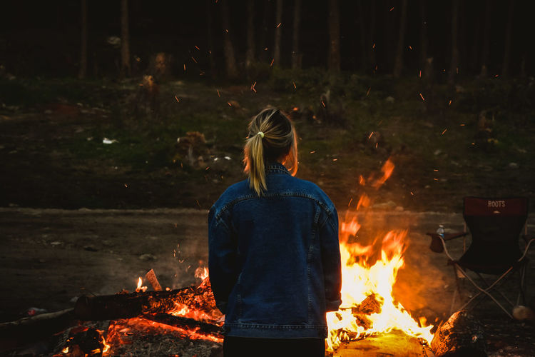Rear view of woman standing by campfire in forest at night