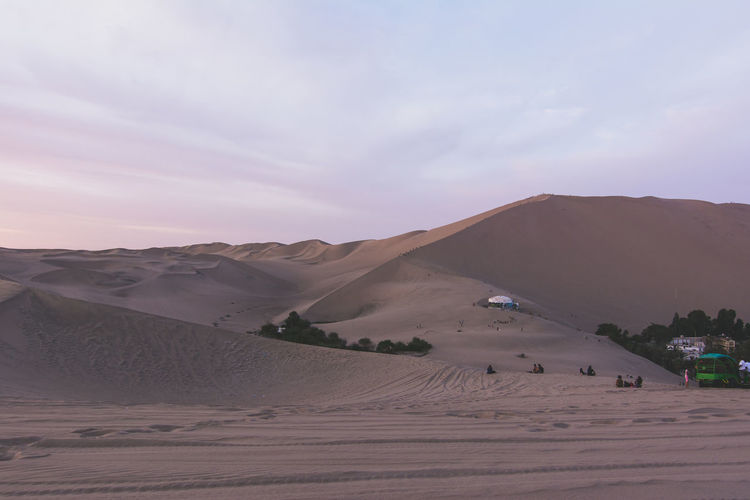 View of sand in desert with tourists