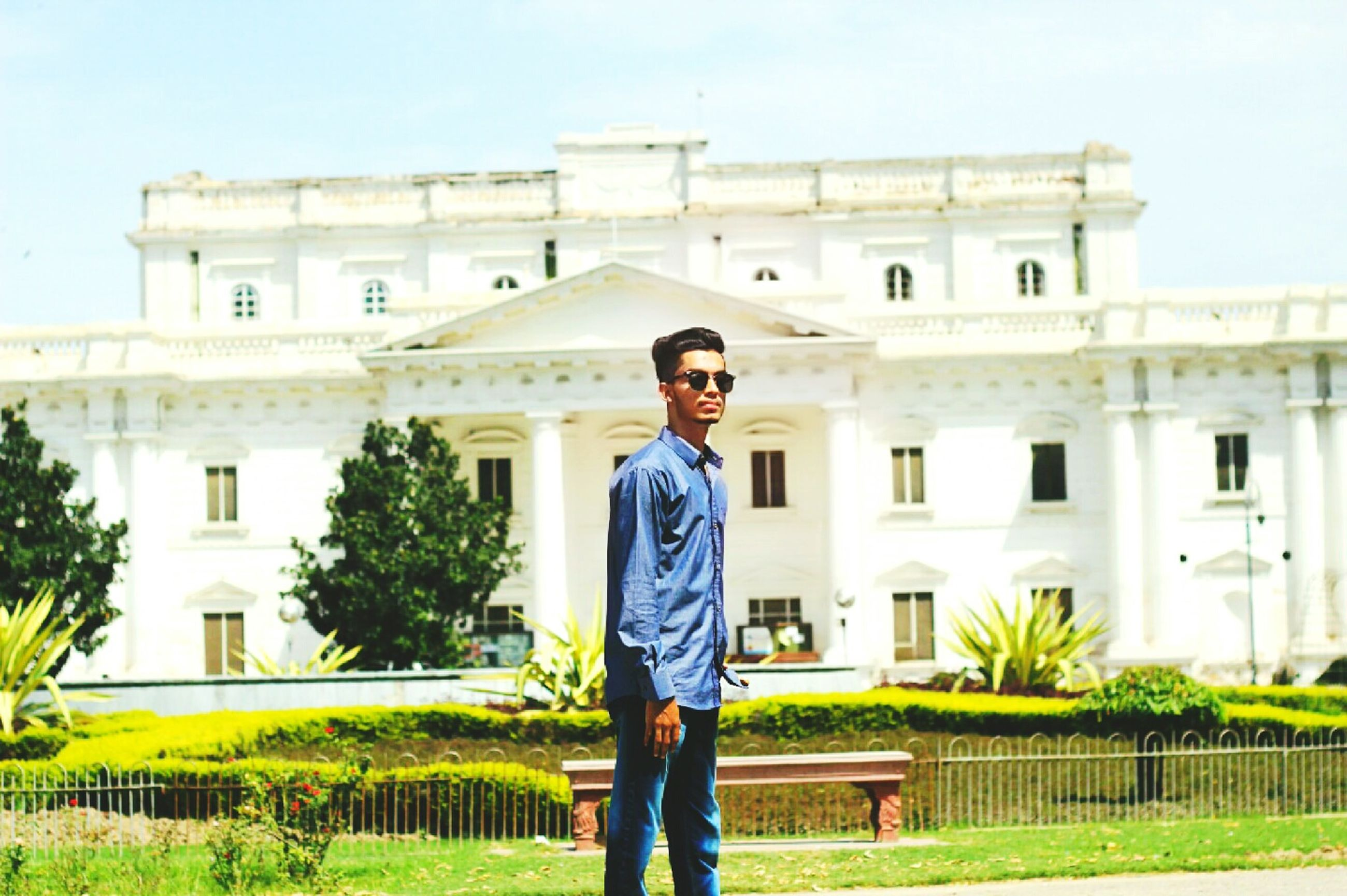 architecture, building exterior, built structure, lifestyles, person, leisure activity, young adult, standing, casual clothing, smiling, sunglasses, front view, residential building, happiness, residential structure, portrait, three quarter length, looking at camera, young women, full length, hands in pockets, clear sky, arch, focus on foreground, in front of, weekend activities, day