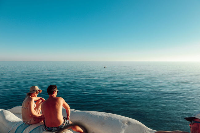 Clear Sky Day Getting Away From It All Heterosexual Couple Horizon Over Water Idyllic Leisure Activity Love Men Nature Outdoors Relaxation Scenics Sea Shirtless Sitting Summer Sunny Togetherness Tranquil Scene Tranquility Two People Vacations Water Weekend Activities