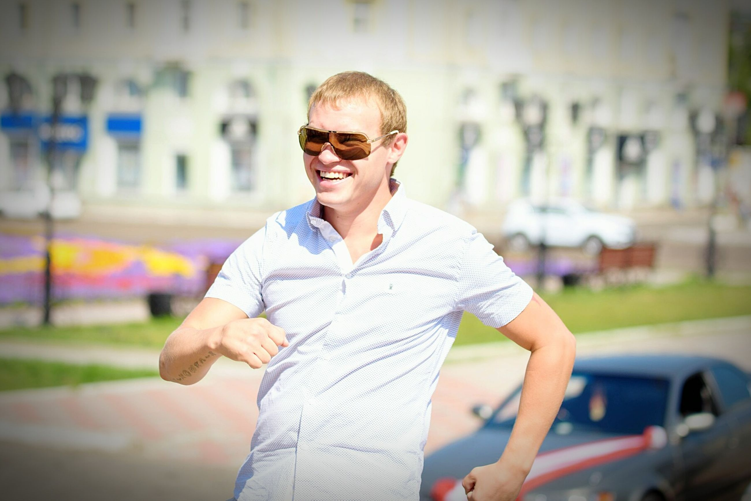 lifestyles, casual clothing, person, young men, young adult, focus on foreground, looking at camera, leisure activity, front view, portrait, waist up, sunglasses, building exterior, smiling, holding, three quarter length, standing, built structure