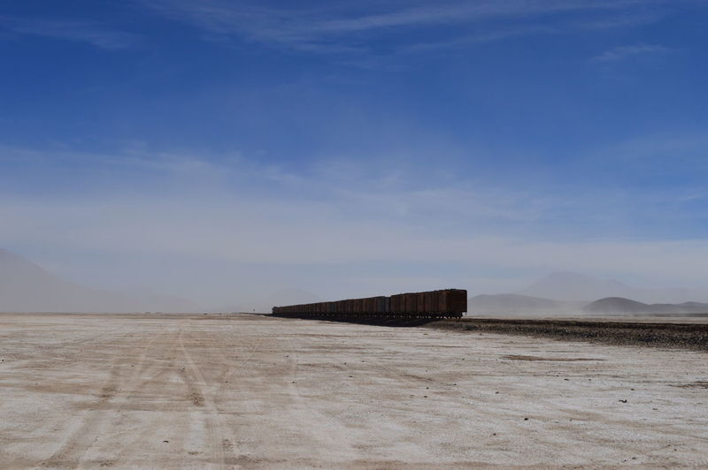 Freight train by beach against blue sky