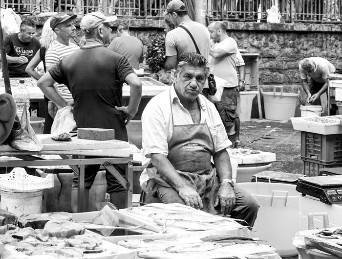at the fish market in Catania, Italy Streetphotography Street Photography Catania Travel Sicily Fish Market Black And White Market Stall Real People Working Adult Travel Destinations