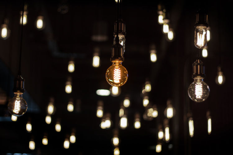Close-up of illuminated light bulbs hanging from ceiling