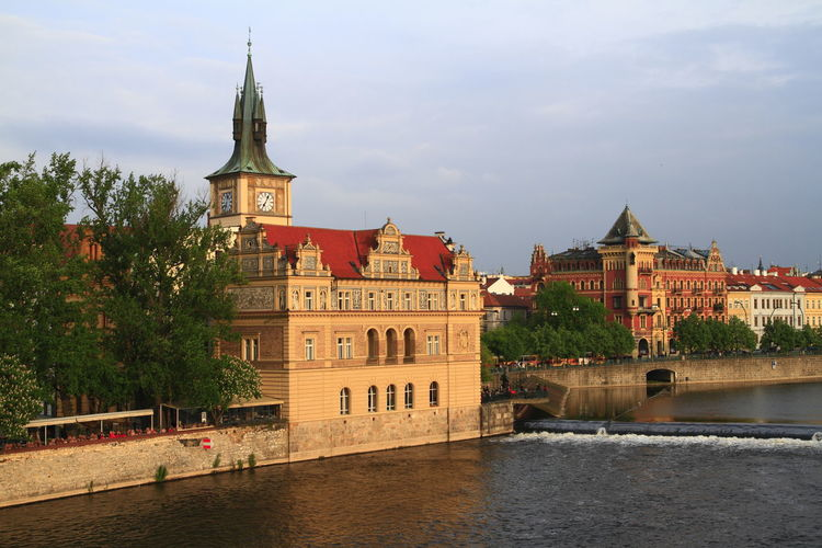 View of buildings by river against sky in city