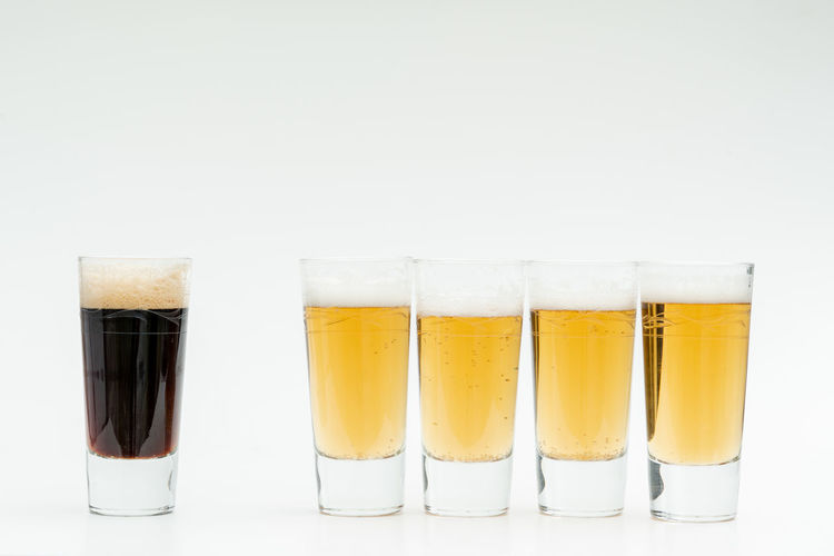 Diversity Drink Refreshment Glass Studio Shot Food And Drink White Background Drinking Glass Household Equipment Indoors  Alcohol Still Life Group Of Objects No People Shot Glass In A Row Glass - Material Beer - Alcohol Choice Copy Space Variation Frothy Drink Beer Glass Clean Lager
