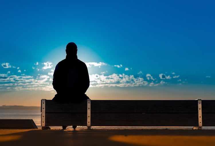 Rear view of silhouette man sitting against sea at sunset