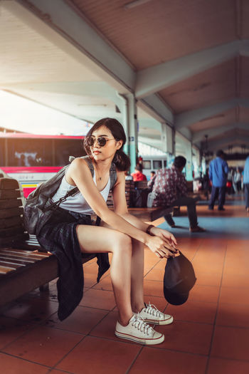 Side view of young woman wearing sunglasses sitting on bench in waiting room