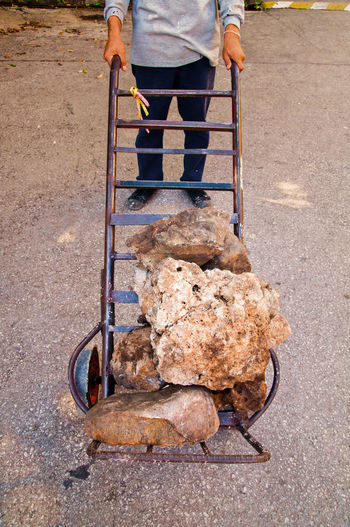 Low Section Of Man Carrying Rocks On Crate While Standing On Ground