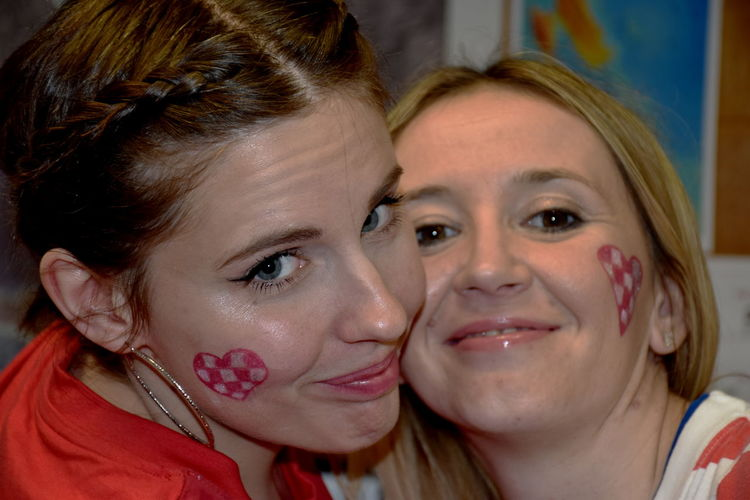 Close-up portrait of smiling female friends with heart shapes on cheeks