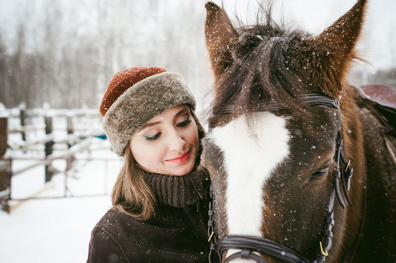 Close-Up Of Beautiful Woman With Horse On Field During Snowfall