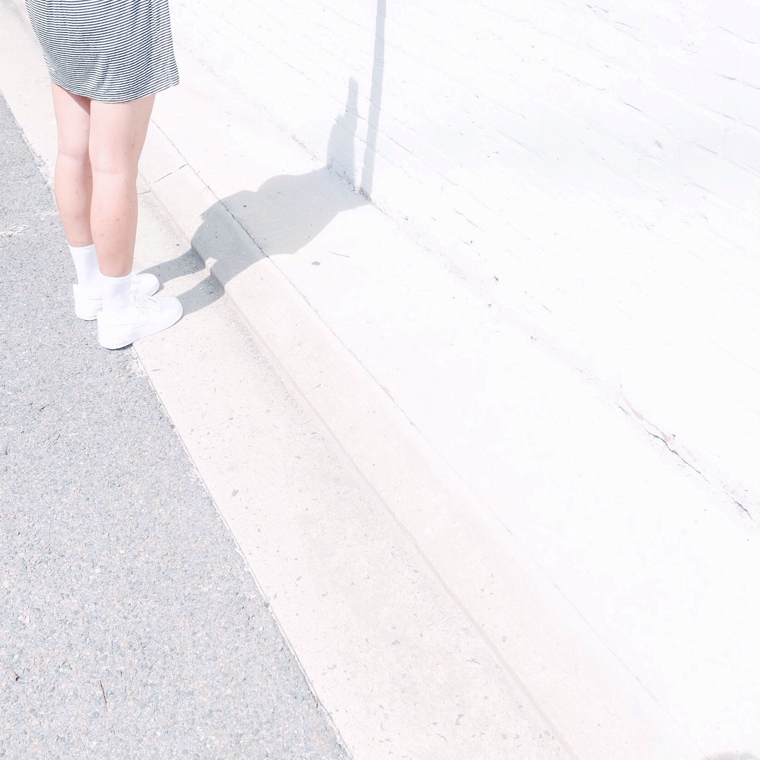 low section, person, lifestyles, standing, leisure activity, walking, shadow, human foot, high angle view, street, men, sunlight, shoe, footwear, day, part of