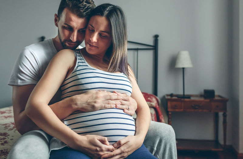 Pregnant woman holding her belly embraced by her husband Baby Care Caress Family Horizontal Love Man Maternity Mother Motherhood Wait Woman Caucasian Expectation Father Female Girl Holding Male Maternal Mom Pregnancy Pregnant Tummy Two People
