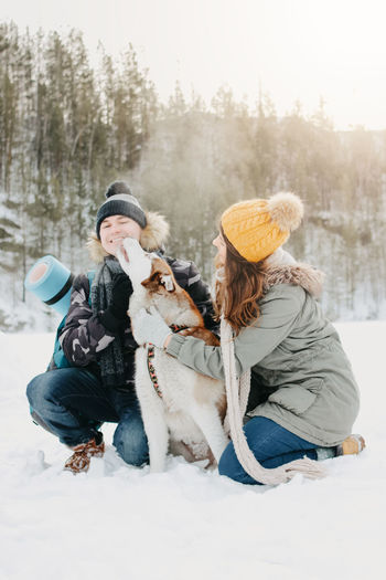Happy couple with dog on snow covered land against clear sky