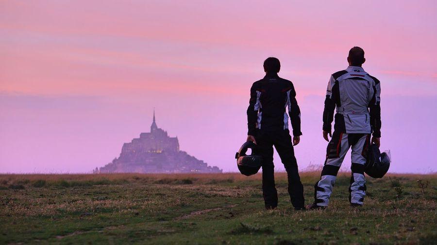 Rear view of men standing on field against sky