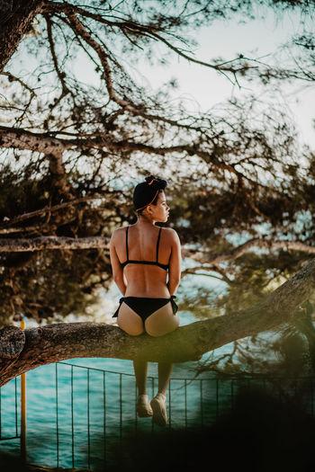 Rear View Of Woman Wearing Bikini While Sitting On Branch Over Sea