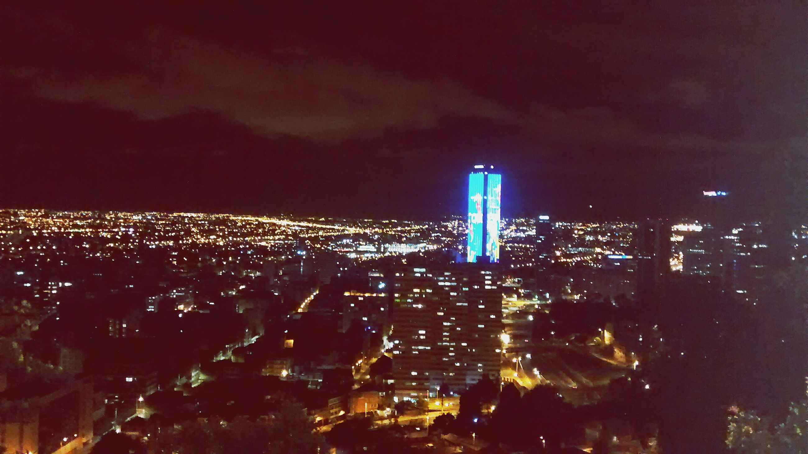 illuminated, night, city, building exterior, architecture, cityscape, built structure, sky, crowded, skyscraper, tower, modern, tall - high, residential district, office building, high angle view, residential building, city life, urban skyline, residential structure
