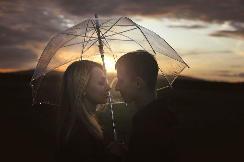 Couple standing below umbrella against sky during sunset