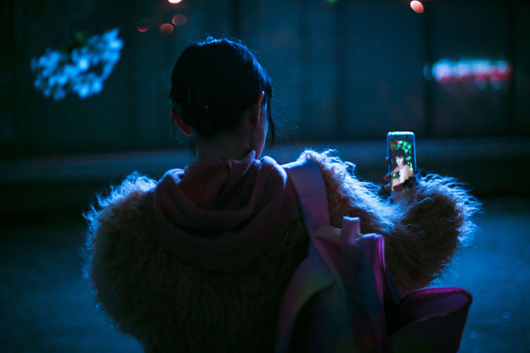 Rear view of woman taking selfie from phone while standing outdoors at night