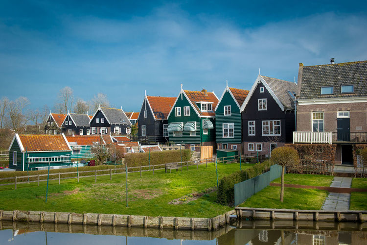 Houses by canal against sky
