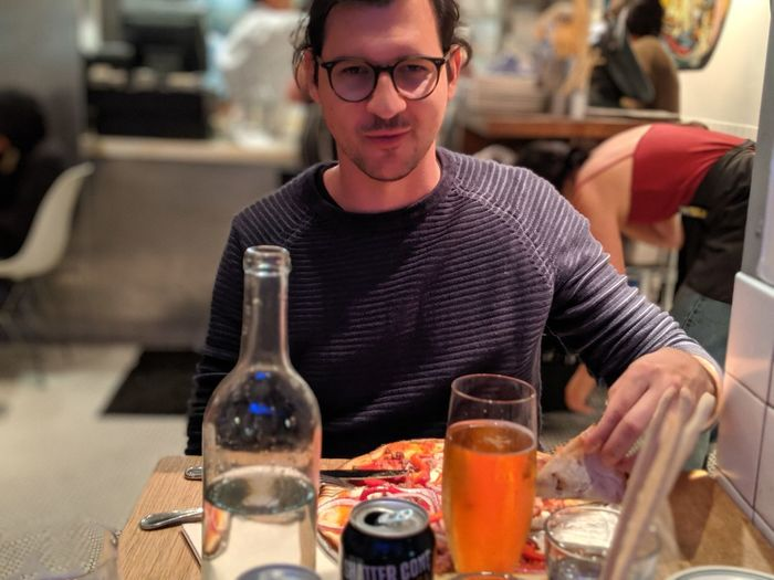 Midsection of man with drink sitting at restaurant table