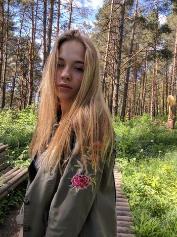 Beautiful Woman Blond Hair Day Forest Front View Leisure Activity Lifestyles Long Hair Nature One Person Outdoors People Real People Tree Tree Trunk Young Adult Young Women