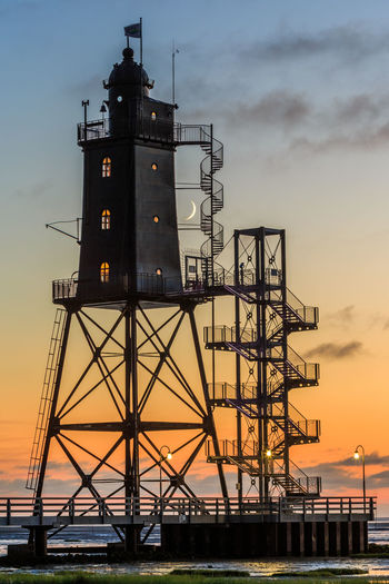 Tower by sea against sky at sunset