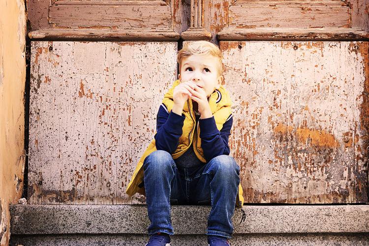 Portrait of boy sitting against wall