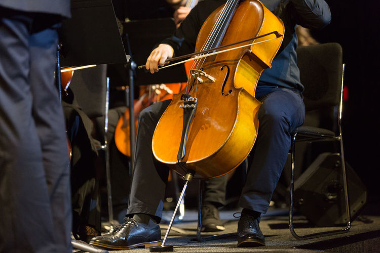Low section of man playing cello on stage