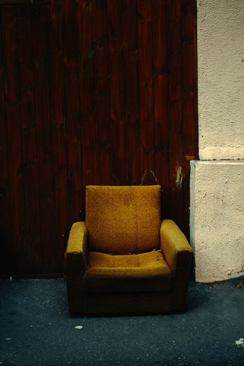 Empty chairs against yellow wall in old building