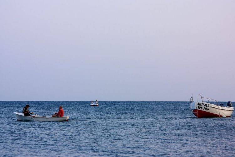 Men sailing in rowboat against clear sky