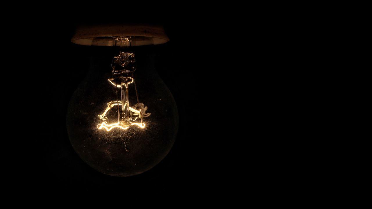 ILLUMINATED LIGHT BULB AGAINST BLACK BACKGROUND