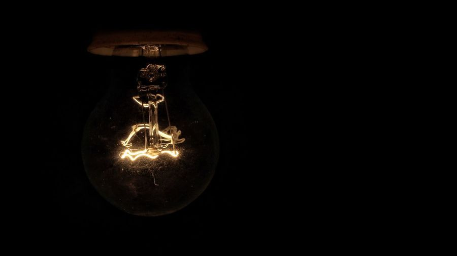 Close-up of illuminated light bulb against black background